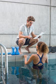 Swimmer talking to her coach poolside — Stock Photo