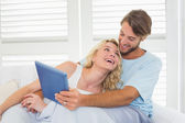Couple on couch using tablet — Stok fotoğraf