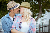 Hip couple kissing by railings — Stock Photo