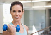 Woman lifting blue dumbbell — Stock Photo