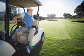 Golfer driving his golf buggy in reverse — Stock Photo