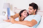Par i sängen med tabletpc — Stockfoto
