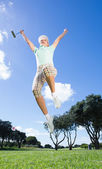 Female golfer leaping and cheering — Stock Photo