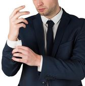 Handsome businessman adjusting cuffs — Stock Photo