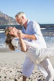 Happy couple dancing on the beach — Stock Photo