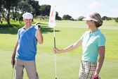 Golfer holding eighteenth hole flag for partner — Stock Photo
