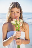 Blonde in sundress smelling roses on beach — Photo