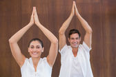 Couple doing yoga with hands raised — Stock Photo