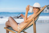 Woman relaxing in deck chair on the beach — Stock Photo
