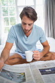 Man reading paper with coffee — Stock Photo