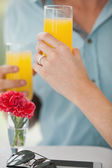 Couple in cafe drinking orange juice — Stock Photo