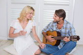 Man serenading girlfriend with guitar — Stock Photo