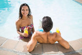 Couple drinking cocktails in the pool — Stock Photo