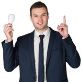 Businessman holding light bulb — Stock Photo