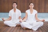 Couple meditating in lotus pose — Foto de Stock