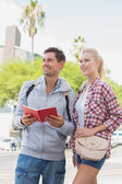 Tourist couple consulting the guide book — Foto Stock