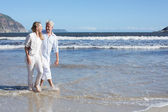 Couple walking barefoot on the beach — Stock Photo