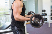 Muscular bodybuilder lifting barbell weight — Stock Photo