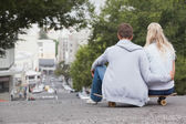 Couple sitting on skateboard — Stock Photo