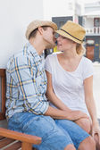 Hip couple sitting on bench about to kiss — 图库照片