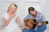Man serenading girlfriend with guitar — Photo