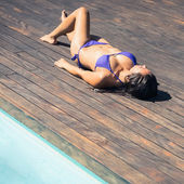 Slim brunette in bikini lying poolside — Stock Photo