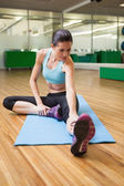 Brunette warming up in fitness studio — Stok fotoğraf