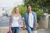 Hip couple on shopping trip walking uphill — Stock Photo