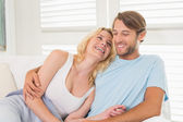 Couple sitting on the couch laughing — Stock fotografie