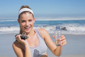 Blonde on beach with bottle and skipping rope — Stock Photo