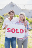 Happy couple holding sold sign — Photo