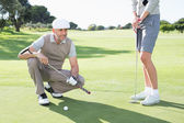Golfing couple on the putting green — Stockfoto
