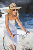 Blonde in sundress on bike at the beach — Stock fotografie