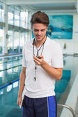 Swimming coach looking at his stopwatch — Stockfoto
