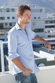 Handsome man looking over his balcony — Stock Photo