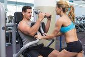Trainer coaching bodybuilder using weight machine — Stock Photo