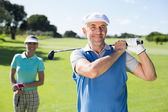 Golfer teeing off with partner behind him — Stock Photo