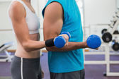 Fit couple exercising with dumbbells — Stock Photo