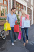 Stylish couple walking with shopping bags — Stock Photo