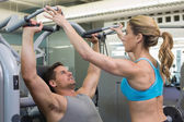 Trainer coaching bodybuilder using weight machine — Stock Photo