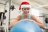Brunette in santa hat leaning on exercise ball — Stock fotografie