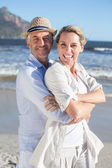 Happy couple standing on the beach — Stock Photo