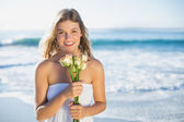 Blonde in sundress holding roses on beach — Photo
