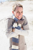 Shivering blonde standing on the beach — Stock Photo