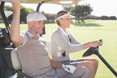 Happy golfing couple  in buggy — Photo