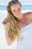 Blonde smiling on beach — Stockfoto