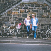 Hip par stående av väggen med cyklar — Stockfoto