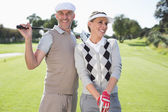 Golfing couple holding clubs — Stock Photo