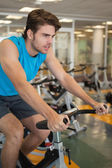 Focused fit man on the spin bike — Stock Photo