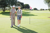 Golfing couple smiling on the putting green — Stock Photo